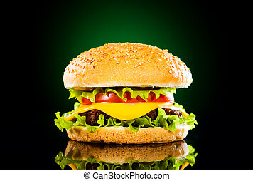 Tasty hamburger and french fries on a dark