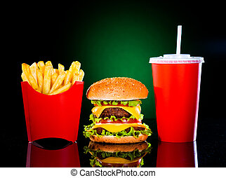 Tasty hamburger and french fries on a dark green