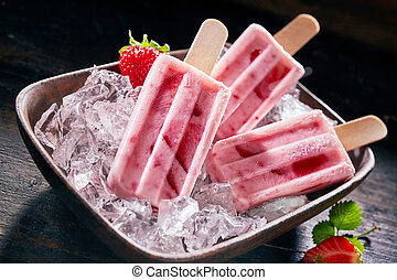 Tasty healthy fresh strawberry popsicles or frozen suckers on a bed of ice in a rectangular dish