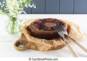Tasty homemade berry cake. Siberian cake with bird cherry, cowberry and black currant in baking paper with lily of the valley flowers on white table with copyspace