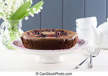 Tasty homemade berry cake. Siberian cake with bird cherry, cowberry and black currant served with lily of the valley bouquet on clean white background with copyspace