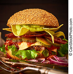 Tasty homemade delicious burger with guacamole and nachos on a wooden table.