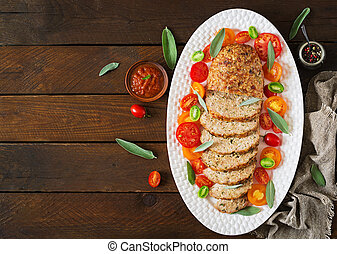 Tasty homemade ground baked turkey meatloaf in white plate on wooden table. Food american meat loaf. Top view. Flat lay