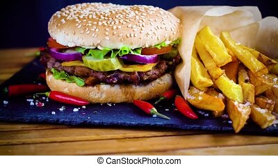 Tasty homemade hamburger with potatos served on stone plate