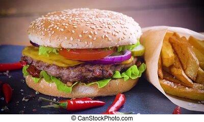 Tasty homemade hamburger with potatos served on stone plate...