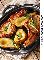 Tasty hot pork chops baked with pears and rosemary in honey sauce in a pan close-up. vertical