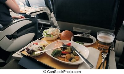 Tasty meal served on board of airplane on the table. Airline...