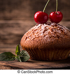 Tasty muffin with cherry and mint on vintage wooden background