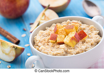 Tasty oatmeal with apples and cinnamon in a bowl