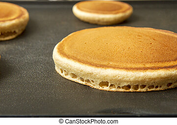 Hot cakes on a griddle cooking for breakfast
