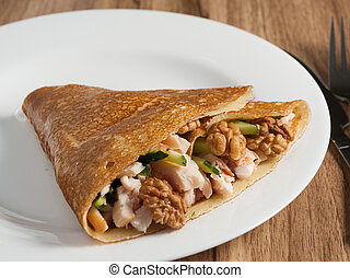pancake with smoked chicken and walnuts on a white plate