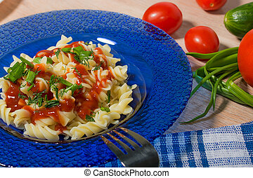 tasty pasta with vegetables and sauce in a blue plate
