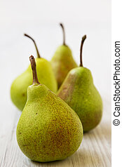 Tasty pears on a white wooden background, side view. Close-up.