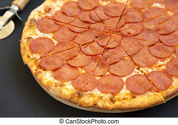 Tasty Pepperoni pizza over black background, side view. Close-up.
