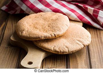 Tasty pita bread. - Tasty pita bread on old wooden table.