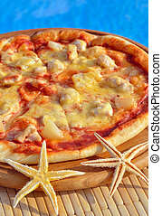 Tasty pizza decorated with starfishes