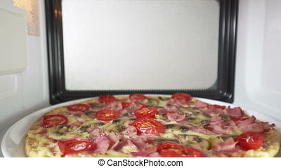 Tasty pizza topped with tomato mushroom and ham heating in microwave oven