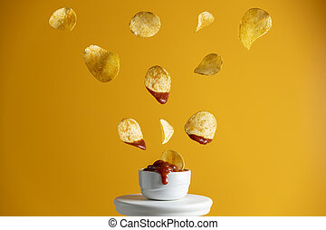 Tasty potato chips falling into blow with tomato sauce, ...