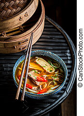 Tasty Red Curry soup in black bowl with chopsticks
