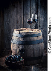 Tasty red wine and grapes and oak barrel