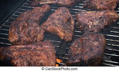 Tasty ribs cooking on barbecue grill for summer outdoor...