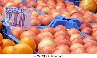 Tasty Ripe large round red apples on a market counter....