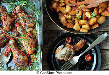 Tasty roasted chicken legs with herbs and fried potatoes
