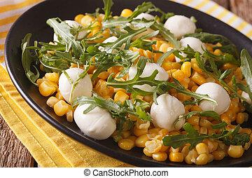 Tasty salad of corn, baby mozzarella and arugula close-up....