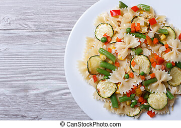 Tasty salad of farfalle pasta with vegetables closeup top view