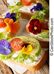 Tasty sandwiches with avocado, tomatoes, edible flowers and cream cheese close-up. vertical