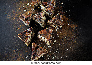 Tasty sliced cake with chocolate on black background