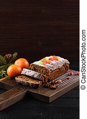 Tasty sliced fruit cake with candied fruits and clementines on dark background copy space