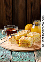 Tasty square layered lemon cake with black tea and lemon curd on shabby wooden background