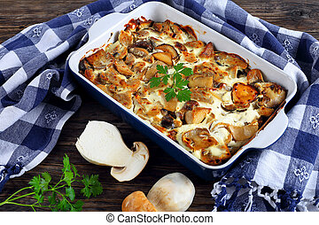 delicious flavorful stew with wild Mushrooms and Sour Cream Sauce in gratin dish on old wooden boards with kitchen towel and fresh raw porcini on background, horizontal view from above, close-up