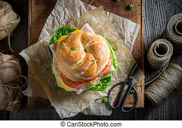Tasty take away sandwich packed in a gray paper
