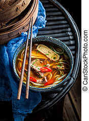 Tasty Thai broth in black bowl with chopsticks