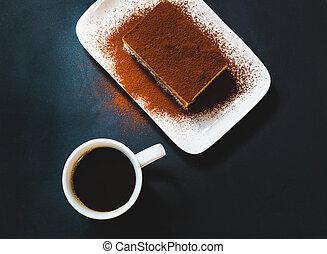Tasty tiramisu cake with coffee cup on black background