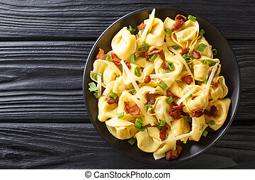 Tasty tortelloni with bacon and cheese close-up in a plate. horizontal top view