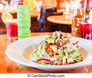 Tasty traditional mexican salad with dressing and red pepper