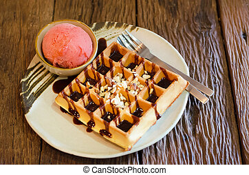 Tasty waffle with scoop of strawberry sherbet ice cream