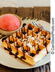 Tasty waffle with scoop of strawberry sherbet