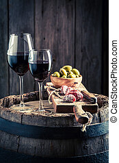 Tasty wine in glass with cold meats and olives on wooden...