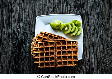 without additions banana waffles served with green kiwi on a white square plate