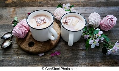 Tasty marshmallow and cups with cocoa near spring flowers