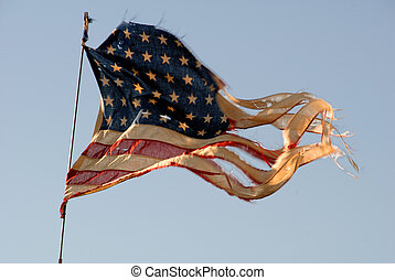 Red, white, and blue, tattered American Flag waving in heavy wind.