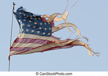 Tattered, ripped and weathered American Flag waving in heavy wind.