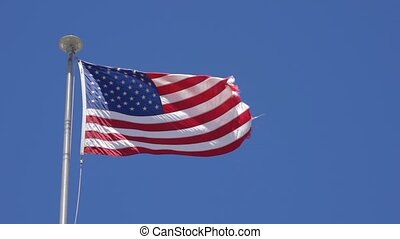 Tattered American Flag Waves in Breeze - Tattered American...
