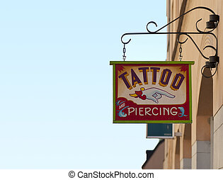 Tattoo and piercing sign outside tattoo parlor