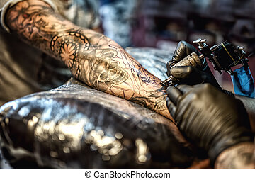 Tattoo artist drawing on arm and on skin of client
