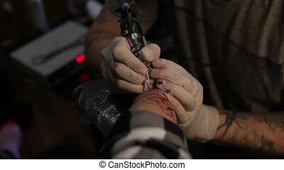 Tattoo artist works in salon - Tattoo artist is making...